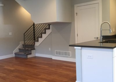 sustainable design build denver colorado west colfax 1275 xavier open concept living room kitchen stairs steel handrail