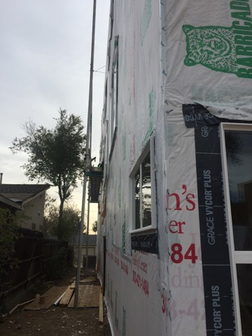 sustainable design build denver colorado west colfax 1254 perry during construction siding install pump jack window