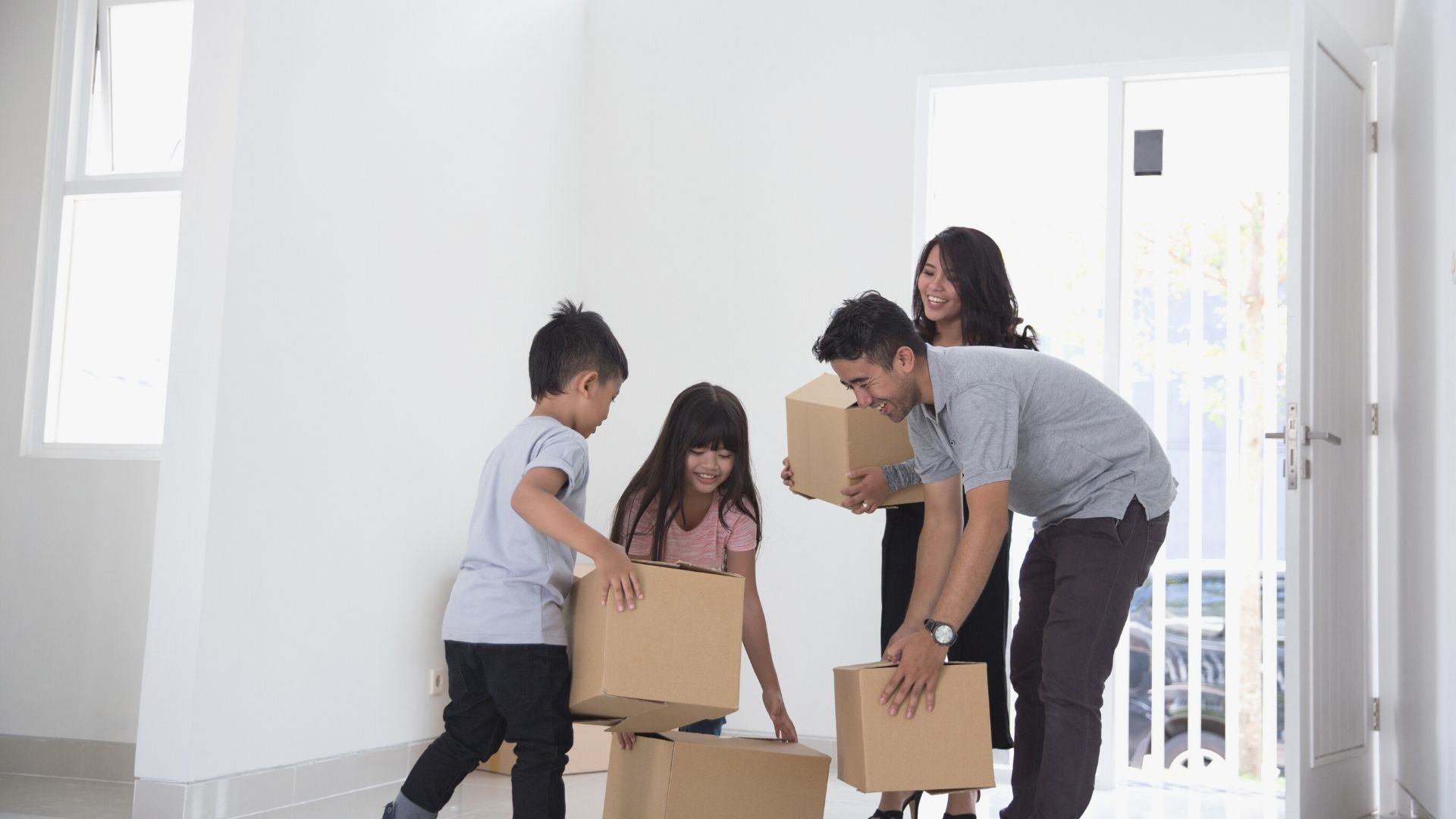Inclusion equality asian family moving in packages boxes white room patio door